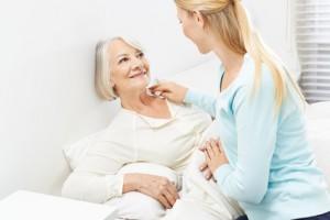 Junge Frau hilft Seniorin bei Körperpflege