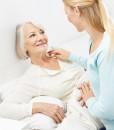 Junge Frau hilft einer bettlägerigen Seniorin bei der Körperpflege