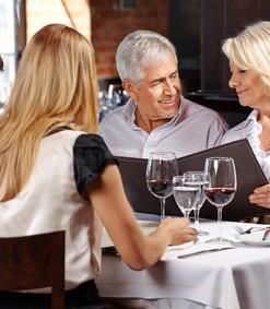 Familie mit zwei Senioren im Restaurant schauen auf die Speisekarte