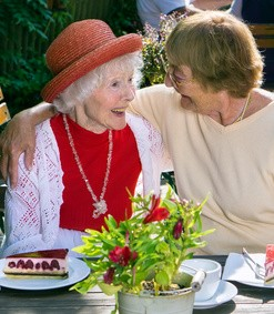 Woman hugging cute laughing friend in red hat in blouse at lunch with plates of cake for dessert in outdoor cafe.