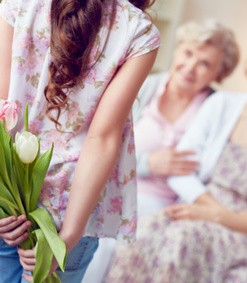 Rear view of little girl holding tulip bouquet behind back while standing in front of her mother and grandmother